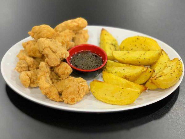 Pollo rebozado en trozos acompañado de patatas al horno y salsa oriental