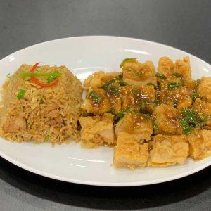 Pollo en trozos rebozados, cebollino, semillas de sésamo y salsa de ostras acompañado de arroz chaufa