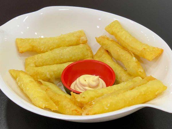 tequeños de masa wantán, rellenos de queso y fritos acompañados de salsa de curry